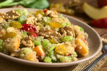 Quinoa Waldorfsalat zubereitet aus gekochtem Quinoa, Apfel, Selleriestangen, Sultaninen und Walnüssen, fotografiert mit natürlichem Licht (Selektiver Fokus, Fokus in die Mitte des Salats)