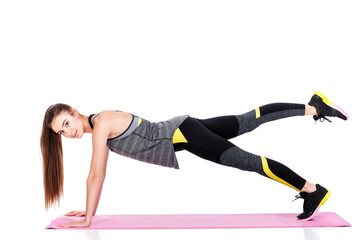 woman in sportswear does exercises on fitness Mat