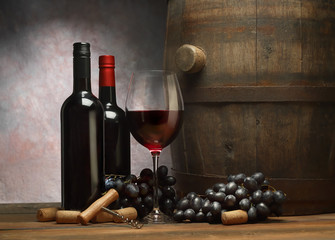 Picture with wine bottles, wineglass of red wine, wooden old barrel and dark grape