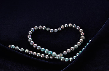 necklace of black pearl in the form of a heart on dark blue velvet