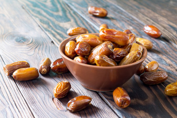 Dried dates in a bowl on a wooden table.
