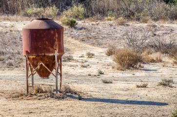 abandoned rusting water tank in a arid field