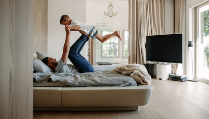Father playing in bed with son