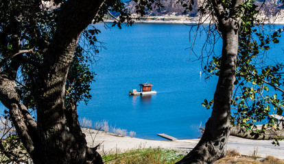 floating dock with tiny cabin in Lake Cachuma, California framed by tree trunks