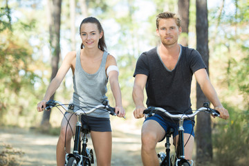 young couple with bicycle in forest