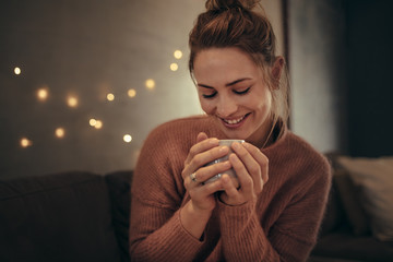 Smiling woman drinking coffee in winter at home