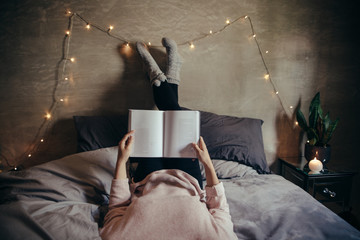 Woman lying on bed and reading book.