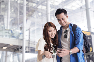 Couple asian student traveler looking or find for flight in smartphone at airport terminal. Check-in by mobile. Teenager are traveling concept.