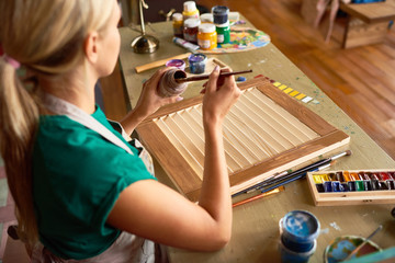 Back view portrait of pretty blonde woman enjoying work in art studio painting shutters with bronze paint, making DIY interior decoration