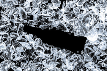 Pieces of crushed ice cubes on black background. Empty space in the center in form of bottle.