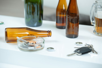 Beer bottles, ashtray and keys on white surface