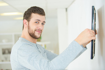 man putting picture frame onto wall