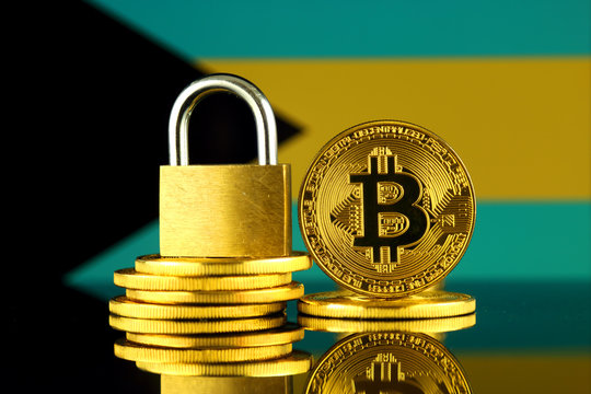Physical version of Bitcoin, golden padlock and Bahamas Flag. Prohibition of cryptocurrencies, regulations, restrictions or security, protection, privacy.