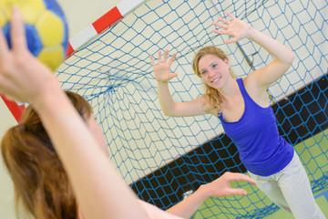 women playing game of handball defending goal
