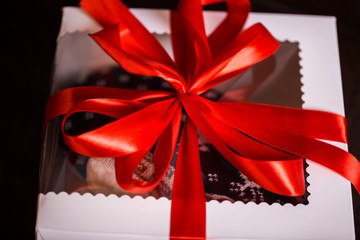Christmas gifts with red bow and christmas illuminations on a black background