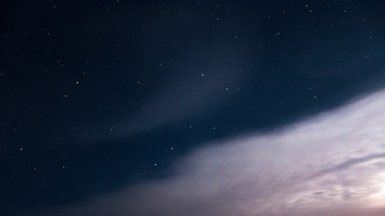 The constellation of a large bear on a beautiful, night, starry sky with clouds.