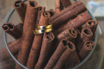 Gold and silver wedding rings on cinnamon sticks