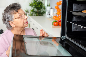 senior caucasian woman opening oven in kitchen