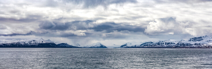 Panorama of clouds over snowy mountains in the arctic