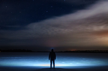 A man with a flashlight on his head is standing and looking at the beautiful starry sky with clouds. In a snowy field. Winter, a frosty night.