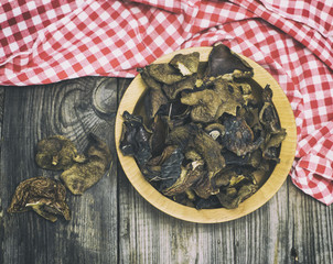 A dried forest mushroom in a wooden plate
