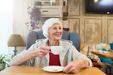 Portrait of elegant senior woman smiling happily looking away sitting in big comfortable chair with tea cup