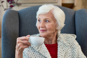 Portrait of elegant senior woman smiling looking away sitting in big comfortable chair with tea cup