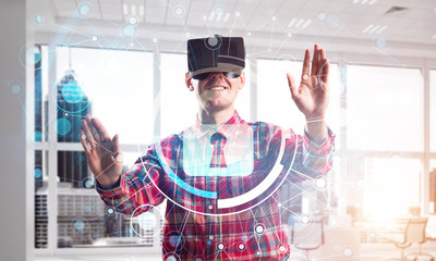 Young man in modern office interior experiencing virtual reality technology