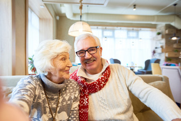 Portrait of happy senior couple holding camera and taking selfie photo on Christmas sitting in cafe