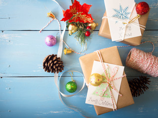 Christmas concept, brown gift boxes with card ,pine cones,jingle bells and glister ball decoration items on blue wooden table  in top view with copy space.