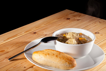 Chicken stew with dumplings and bread roll. Hot comfort food.