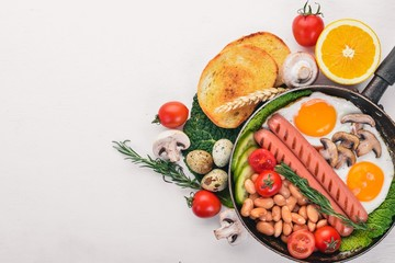 English breakfast tomatoes, sausages, beans, mushrooms, eggs,toast and herbs top view. On a white wooden background.