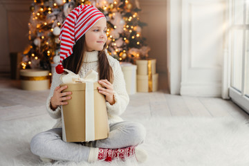 Adorable female child wears santa claus hat, warm clothes, hold wrapped gift box, sits against decorated New Year tree. Happy pretty kid looks aside out of window, sits crossed legs on floor
