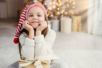 Horizontal portrait of adorable little child, leans on hands with present box, sits against decorated Christmas tree. Blue eyed small kid in knitted white sweater poses at camera. Holidays concept