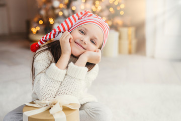 Beautiful small child poses in living room, leans at present gift, has happy expression, glad to recieve surprise from parents, spends holidays in family circle. Merry Christmas and happy New Year
