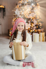 Vertical portrait of beautiful pleasant looking small child wears knitted sweater and socks, sits crossed legs with present, has desire to wrap it, being in living room near decorated New Year tree
