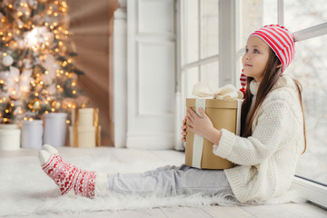 Sideways portrait of restful female child wears white sweater, trousers and warm socks, embraces wrapped gift, sits on floor in cozy room, admires New Year tree. Children and holidays concept