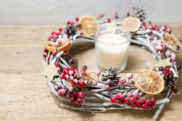 Decorative winter wreath with red berries, cones and slices of orange