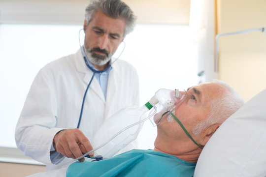 doctor helping an collapsed man wearing a breathing mask