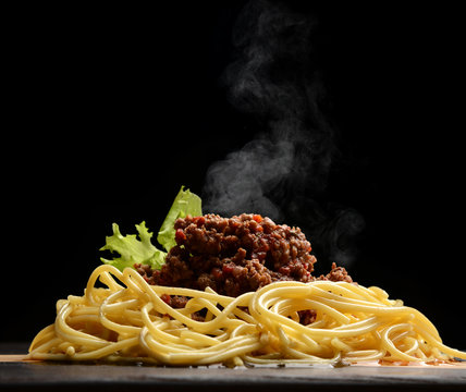 spaghetti Bolognaise or Bolognese with savory minced beef and tomato sauce garnished with salad and steam smoke
