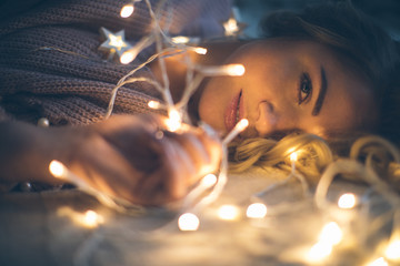 A beautiful thoughtful woman looks with an expressive look on the bed amongst lights. shallow depth of field Wall mural