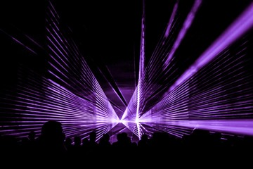 Purple laser show nightlife club stage with party people crowd. Luxury entertainment with audience silhouettes in nightclub event, festival or New Year's Eve. Beams and rays shining colorful lights