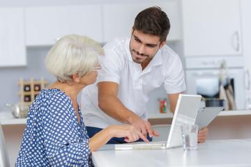 adult grandson teaching his grandma using a computer