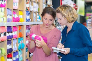 women customer choosing various yarn in sewing store