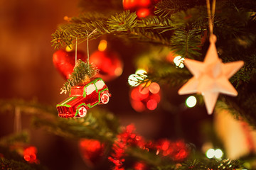 Miniature Toy Car carrying a Fir Tree hanging in Christmas Tree