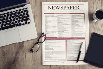 Newspaper with computer on wooden background