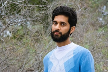 Middle eastern thick bearded male model wearing light blue sweater with dry tree background