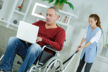 disabled man at home using laptopwoman cleaning in background