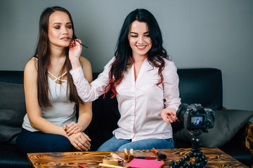 Young female blogger with her client doing makeup cosmetics and recording video at home