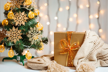 A Christmas tree decorated snowflakes and a garland, gift with knitted scarf on the background of a bokeh and white boards. Merry Christmas, ideas for postcards for winter holidays
